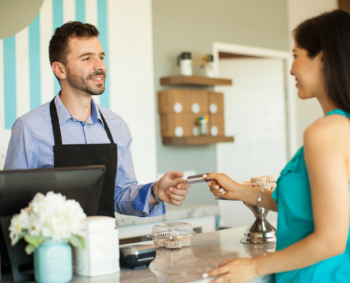 woman-using-gift-card-at-small-cafe