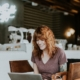 young-professional-female-smiling-at-computer-screen-in-cafe